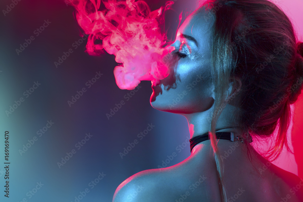 Fototapeta Fashion art portrait of beauty model woman in bright lights with colorful smoke. Smoking girl