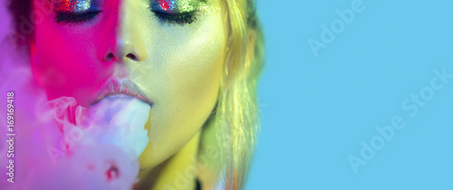 Fashion art portrait of beauty model woman in bright lights with colorful smoke. Smoking girl