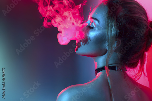 Fotobehang Rook Fashion art portrait of beauty model woman in bright lights with colorful smoke. Smoking girl