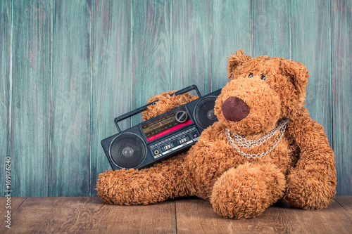 Photo  Retro Teddy Bear toy and old outdated ghetto blaster radio recorder from 80s front grunge wooden wall background