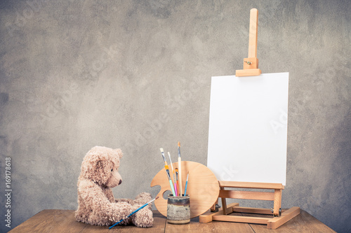 Teddy Bear toy, portable desk easel for painting with canvas blank, brushes and artist's palette on wooden table front concrete wall background. Retro instagram old style filtered photo