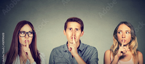 Fotografie, Obraz  Secretive young people man and two women with finger to lips gesture