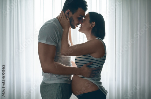Fotografia, Obraz  Man embracing and kissing his pregnant woman