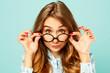 Leinwanddruck Bild Pretty smiley girl wearing glasses over blue background