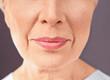 Leinwandbild Motiv Closeup view of beautiful elderly woman on gray background