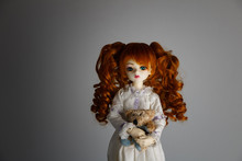 A Doll With Lush Red Hair In An Antique Dress