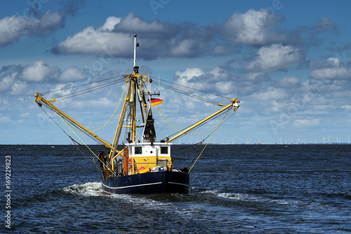 crabs or shrimp fishing boat on the North Sea under a blue sky with clouds, copy space