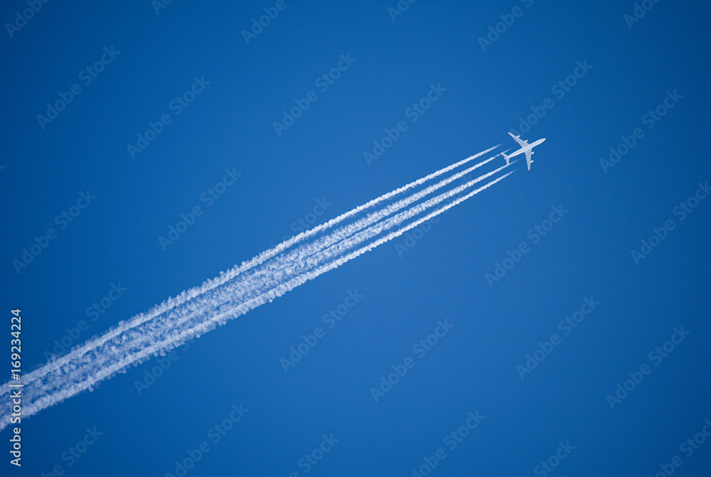 Fototapety, obrazy: A jet plane flying overhead diagonally with condensation trail.