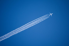A Jet Plane Flying Overhead Diagonally With Condensation Trail.