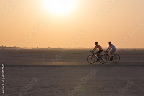 Foto op Plexiglas Fietsen Cycling in the desert at sunset