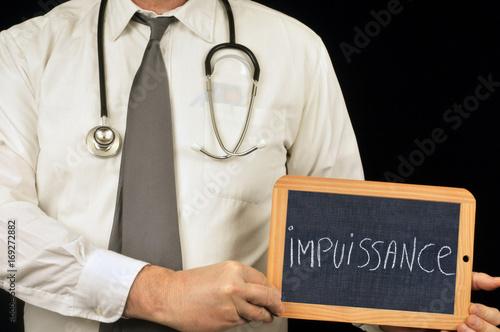 Fotografie, Obraz  Médecin tenant une ardoise sur laquelle est écrit impuissance