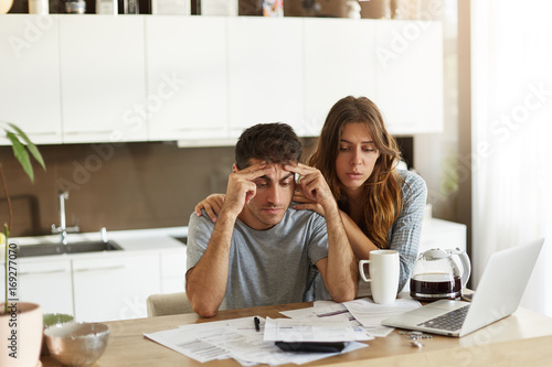 Fototapeta People, relationships, debts, financial stress and economic crisis. Unemployed young Caucasian man feeling depressed, sitting at kitchen table over unpaid bills while his wife trying to cheer him up obraz