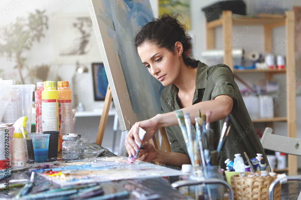 Fototapeta Picture of serious concentrated young Caucasian female artist sitting at desk with painting accessories, holding tube of oil paint, mixing colors on palette; unfinished painting on canvas near her
