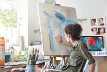 Art, Creativity, Hobby, Job And Creative Occupation Concept. Rear View Of Busy Female Artist Sitting On Chair In Front Of Easel, Painting With Fingers, Using White And Blue Oil Or Acrylic Paint