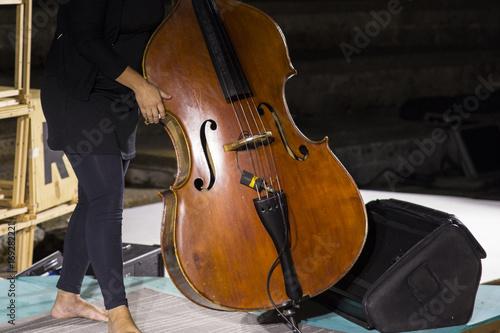 Fototapeta Szczegóły kontrabasu, instrument muzyczny rodziny strunowych łuków. Basista układa instrument muzyczny i ma go oddać przed rozpoczęciem koncertu.