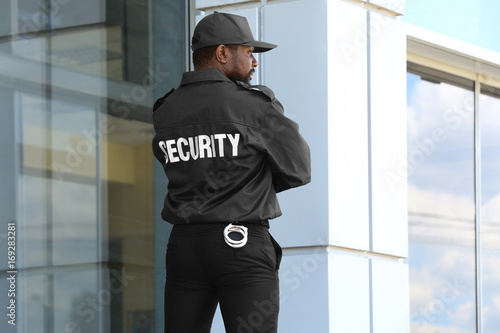 Fotografia  Male security guard standing near big modern building