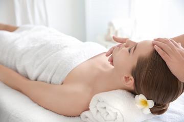 Obraz na płótnie Canvas Young woman enjoying of facial massage in spa salon