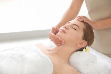 Fototapeta na wymiar Young woman enjoying of facial massage in spa salon