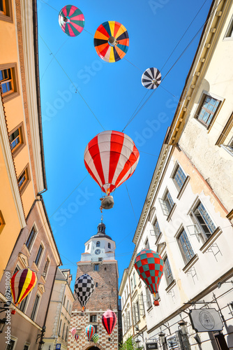 Obraz Lublin, Poland - August 10, 2017: Beautiful street and old bright buildings in the old town of Lublin, Poland. View on Cracow gate, Lublin. Mountebanks Carnaval in Lublin old town. - fototapety do salonu