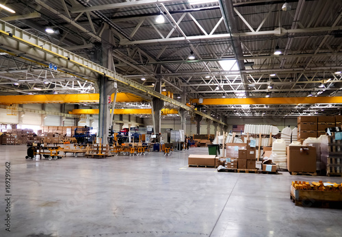 Fotografie, Obraz  Warehouse industrial premises for storing materials and wood, there is a forklift for containers