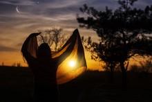 Back View Of Muslim Woman Praying .Praying Time . Glowing Sunset . Ramadan Kareem . Ramadan Background . Arab Night