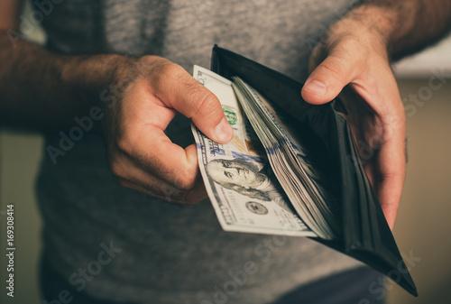 Fotomural  Man looks in the wallet
