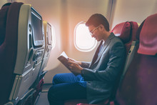 Young Asian Business Man Smiling And Reading A Book In Airplane