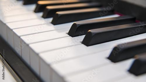 Obraz na płótnie Fragment kluczy starożytnego fortepianu, ale odnowiony i odnowiony. Klawiatura składa się z 88 klawiszy w czerni i bieli, na których odbijają się ciepłe kolory zachodu słońca.