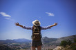 Woman standing on a mountain peak with wide spread hands