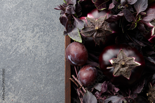 Photo Wooden tray with purple vegetables and herbs on stone textured background