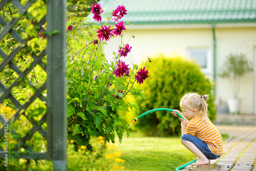 Cute little girl watering flowers in the garden at summer day. Tapéta, Fotótapéta