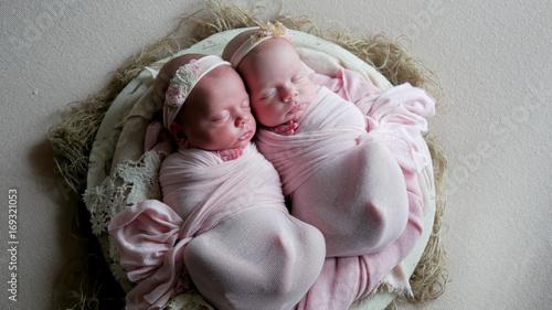 Plakat bliźniaczki dzieci śpią w łóżeczku w sukienkach i opasce