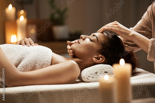 Fotografía  Attractive african girl enjoying face massage in spa salon.