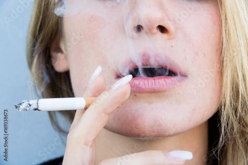 primo piano di una bocca mentre fuma una sigaretta ,ragazza bionda