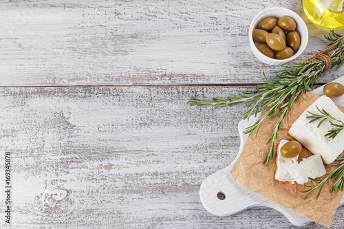 Fresh feta cheese with rosemary on white wooden serving board