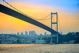 bridge through the Bosphorus strait in the evening on a sunset, on a background business cent of Istanbul