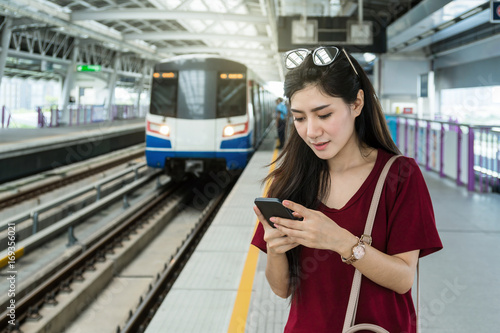 Photo  Asian woman passenger with casual suit using the social network via smart mobile
