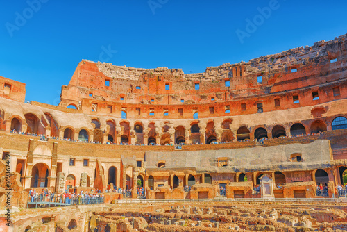 Tourist's Inside the amphitheater of Coliseum in Rome- one of wonders of the world  in the morning time Wallpaper Mural