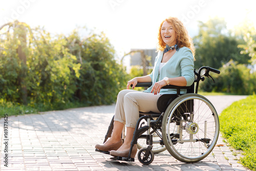 Foto  Chrerful wheelchaired woman laughing in the park