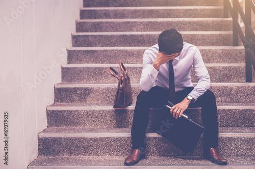 Fotografia stressed businessman holding portfolio sitting at stairway