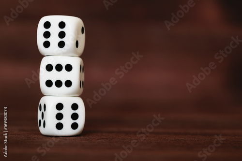 Three white plastic dices on each other on brown wooden board background Poster