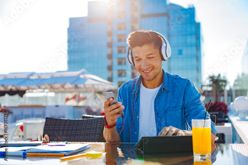 Photo  Cheerful young man working and enjoying music