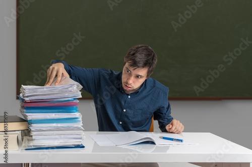 Plakat Zmęczony i wyczerpany nauczyciel poprawia wiele egzaminów w klasie.
