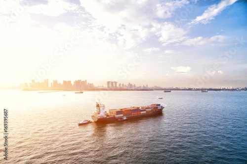 Photo  tranquil sea with container ship with sunbeam