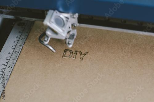 Fotografía  Laser engraving DIY (Do It Youfself) word on recycle cardboard