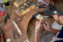 High Angle Portrait Of Jeweler Making Flower Ring In Workshop, Forming And Polishing It On Work Station With Different Tools