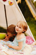 Girl hugs boy sitting under the tent during picnic