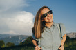 Charming Woman traveler with blue backpack and sunglassesagainst amazing mountains
