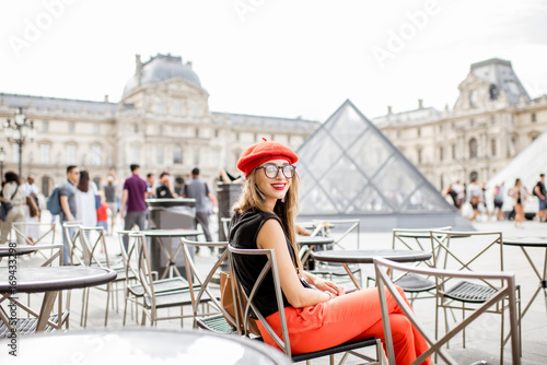 Young woman tourist in red cap sitting near the famous Louvre museum in Paris Tableau sur Toile