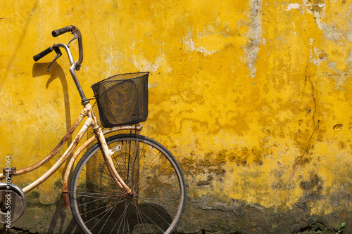 Türaufkleber Fahrrad Old bicycle against old yellow wall on a street of Hanoi old town, Vietnam.